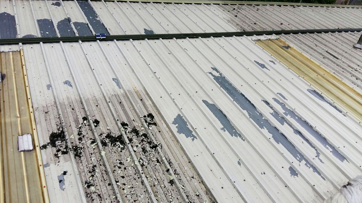 dirty commercial roof system needs maintenance to clear debris